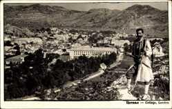 Postcard Cetinje Montenegro, Mann in Tracht mit Ortschaft im Hintergrund