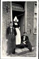 Ak Edam Volendam Nordholland, Frau und zwei Männer in Tracht vor einem Haus